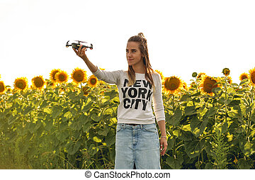 Beautiful woman is holding a mini dron on the background of...