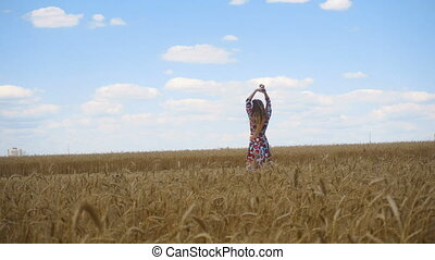 good beautiful girl in dress stands out in the field and...