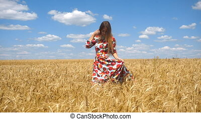 girl holding hands bright dress and goes to wheat field -...