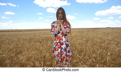 girl stands in the field dress and shows in the palms, wheat...