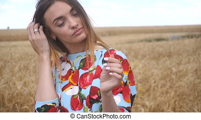 young woman holding a wheat spikelet and twists close-up -...