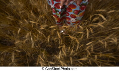 girl is standing in a field and stretches in the hands to...