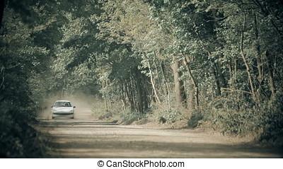 Small White Sedan Running on Gravel Forest Road Stirring Up...