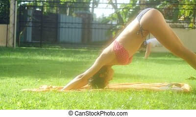 Beautiful young slim women doing yoga on the grass in the shine morning.
