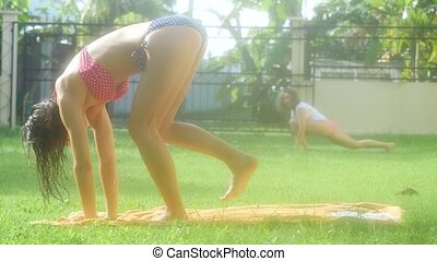 Beautiful young slim women doing yoga on the grass in the shine morning. 4k, 3840x2160