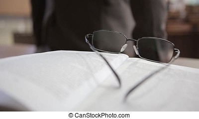 White notebook with glasses on wooden table. Glasses teacher...