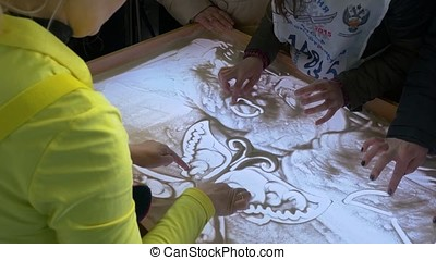 Woman doing sand painting on glass 4K