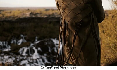 Close-up back view of young woman standing in front of Barnafoss waterfall in Iceland. Fringe from jacket waves on wind.