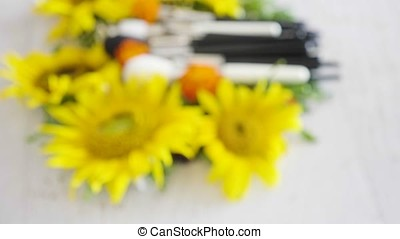 Brushes for makeup on a table next to flowers