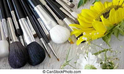 Make-up brushes on a table with spring flowers arround