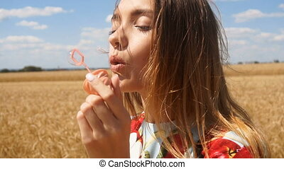 young woman smiles and puskat soap bubbles in slow motion