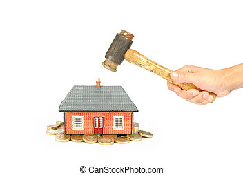 House market crisis - Hammer smashing a miniature house on a...