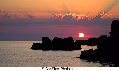 Sunset Over the Sea with Rocks and Clouds