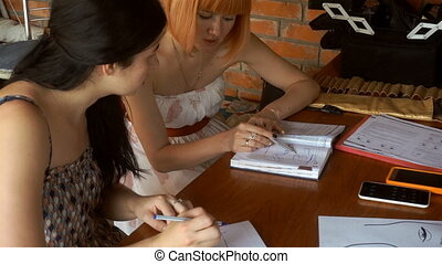 two girls studying form and correction of eyebrows - two...