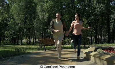 Joyful couple running in the park