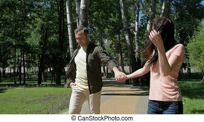 Pleasant couple walking outdoors - Hold my hand. Positive...