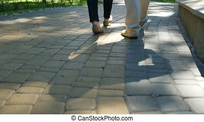 Low angle of loving couple walking in the park