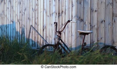 Old rusty bicycle on the background of a wooden fence. Andreev.