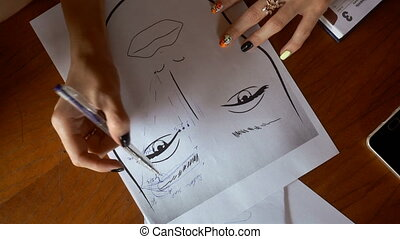 makeup artist draws on paper eyebrows - a young makeup...
