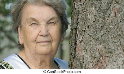 Portrait of serious old elderly woman in forest