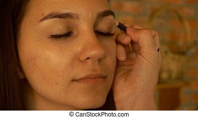 makeup artist draws a pencil eyebrows young beautiful girl...