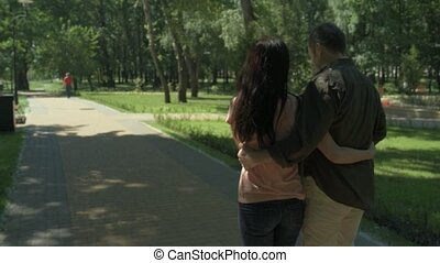 Rear view of positive loving couple walking in the park