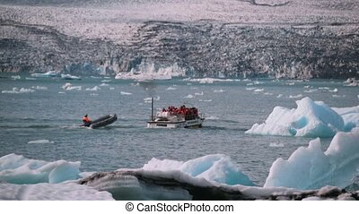 A group of tourists on a boat sail to the shore of Iceland....