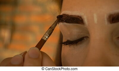 girl paints the thick dark eyebrows special professional...