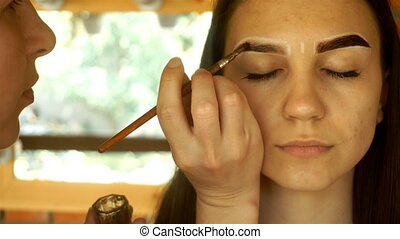 Professional makeup artist holding a brush and paint the...