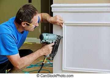 Carpenter using a brad nail gun to complete framing trim Air...