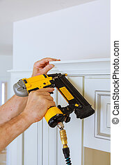 Carpenter brad using nail gun to Crown Moulding on kitchen...