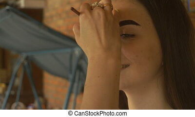 beautiful smiling girl sits on painting the eyebrows...