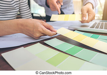 Two colleagues interior Creative creativity graphic designer working with graphics laptop, blueprint and colour chart at workplace on wooden desk , colour ideas style concept