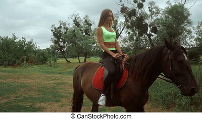 young girl rides on horseback at daytime