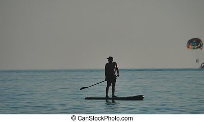 man is floating while standing in the ocean paddle board. by...