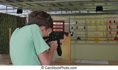 Boy teen shoots in a dash from the machine gun. Airguns gun....