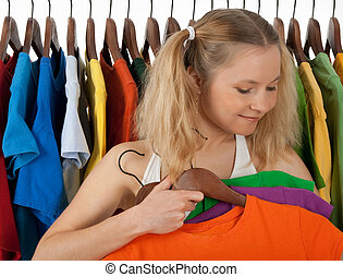 Girl choosing clothes in a store - Girl standing near the...