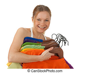 Charming young woman holding colourful clothes - Charming...