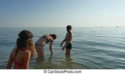 Family bathe in the sea. The boy stumbles in water a funny...
