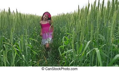 Girl happiness. Girl teenager runs along a green field with...