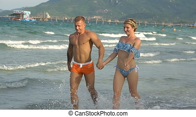 Attractive cheerful couple walking at beach.