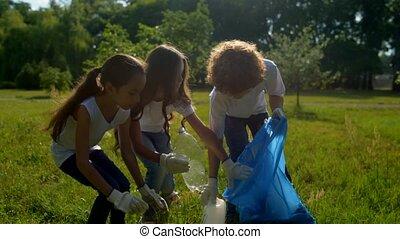 Little volunteers putting trash in garbage bag - Clean and...