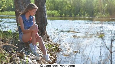 Girl on the river bank. Woman sits by the water nature...