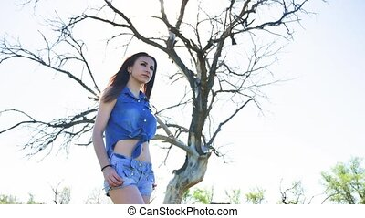 Sexy girl. Girl standing on nature in shorts and shirt on...