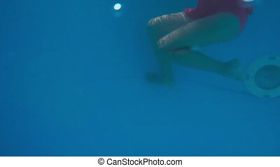 The little girl in the water park swimming underwater and...