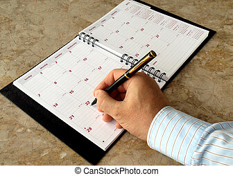monthly planner - Man filling out monthly planner on the...
