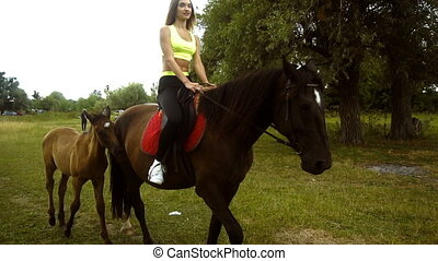 girl riding her horse with foal walks aside outdoors