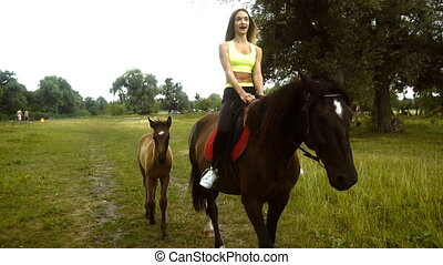 Charming girl riding her horse with foal walks aside...