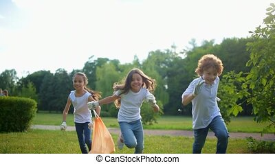 Excited children running fast with garbage bag in hand - Fun...