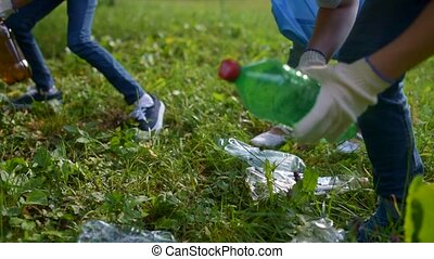 Close up of young ecologists keeping mother earth clean -...